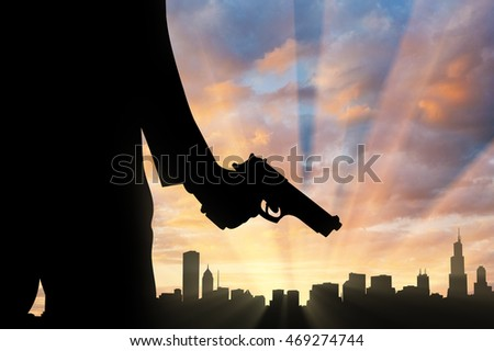 Terrorist concept. Pistol in hand terrorist, against the background of the urban landscape at sunset