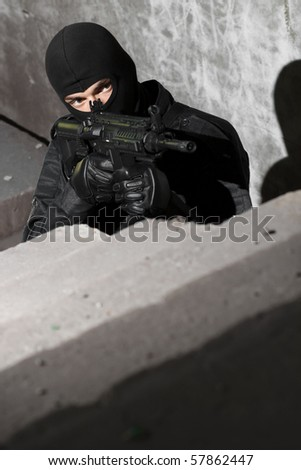 Terrorist in black mask and uniform targeting with automatic American M-4 rifle in the ruined building. Warfare in Ukraine, unknown armed forces