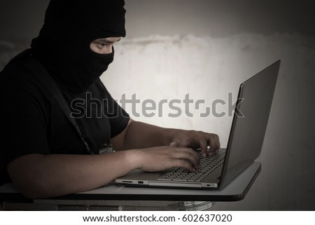 Terrorist in black mask with gun and working on his computer.