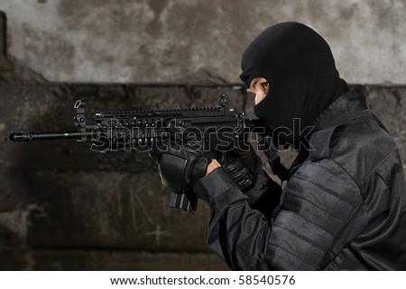 Terrorist in black uniform targeting with M-4 rifle - stock photo