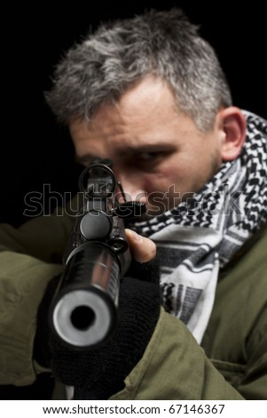 Terrorist in shemagh whit gun, isolated in black background - stock photo
