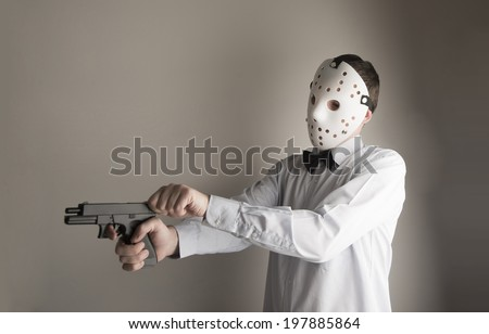 terrorist.male figure wearing platik horror mask Man holding with a black metal pistol isolated on a gray background. Dramatic light Copy space for inscription - stock photo