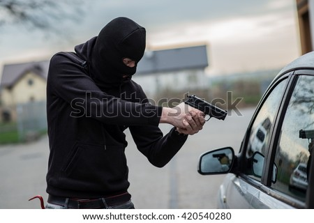 Terrorist or a car thief pointing a gun at the driver - car owner - stock photo
