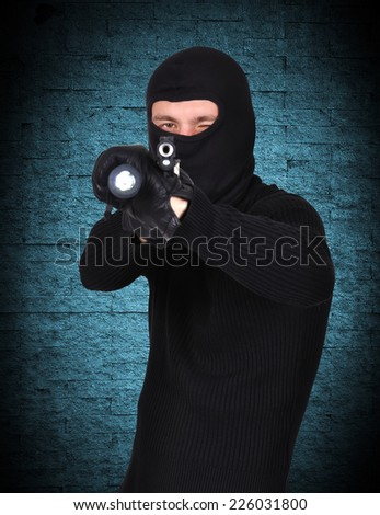 terrorist with gun and flashlight on a blue background - stock photo