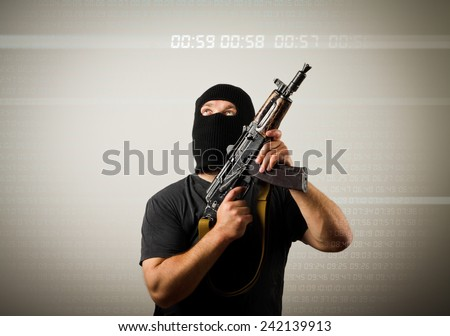 Terrorist with gun looking at a digital clock. Time concept.