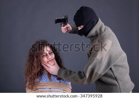 terrorists holding a gun and threatens woman - stock photo
