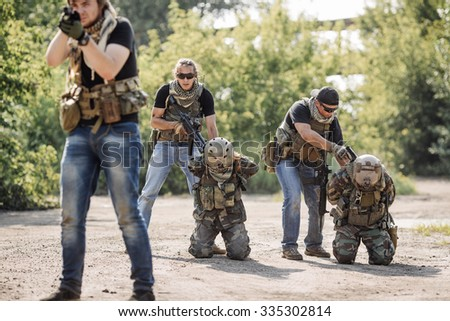 Terrorists with weapon captured soldiers hostage