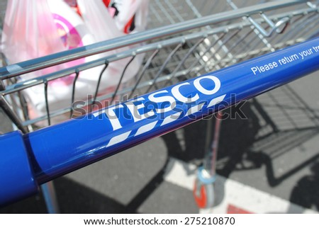 Tesco supermarket shopping trolley with a small amount of shopping inside. Taken on April 26th 2015 in Dudley. Tesco is facing dwindling sales following stiff competition from budget supermarkets - stock photo