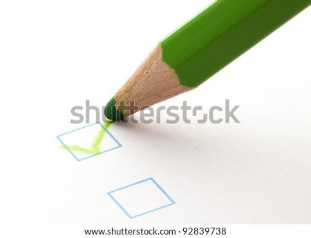 test check box and green crayon, closeup photo - stock photo