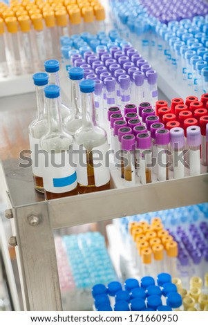 Test tubes and bottles arranged on medical trolley - stock photo