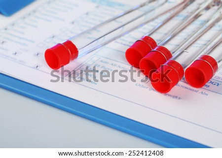 Test tubes and clipboard with medical history form close up - stock photo