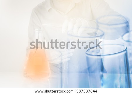 test tubes in scientist hand with pour chemicals in flask at a lab