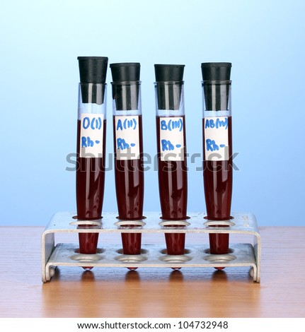 Test-tubes with blood on wooden table on blue background - stock photo