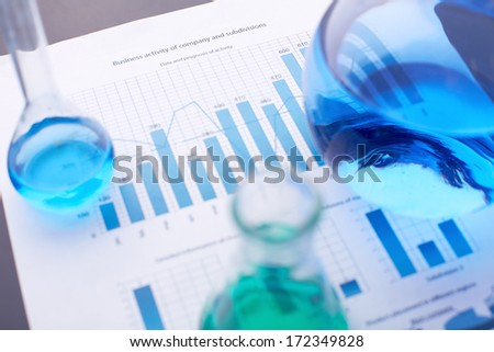 Test-tubes with blue liquids over business document - stock photo