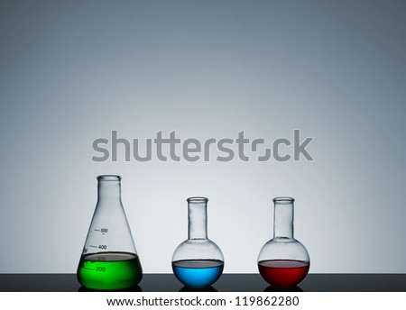 test tubes with colored liquid on a gray background, a still life, a place for text
