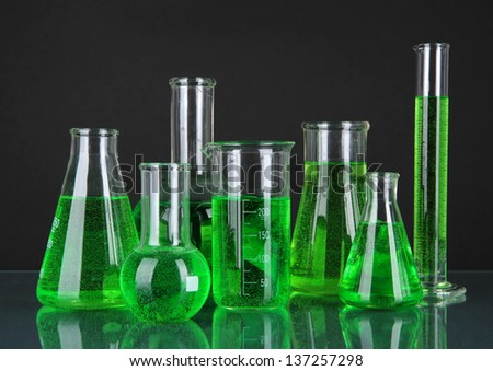 Test-tubes with green liquid on dark gray background
