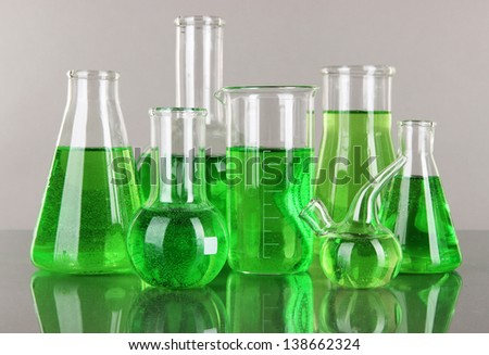 Test-tubes with green liquid on gray background