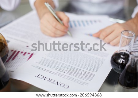 Test-tubes with liquid oil and paper agreement being signed by human - stock photo