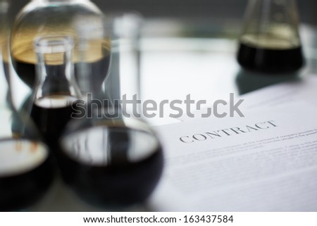 Test-tubes with liquid oil and paper agreement near by - stock photo
