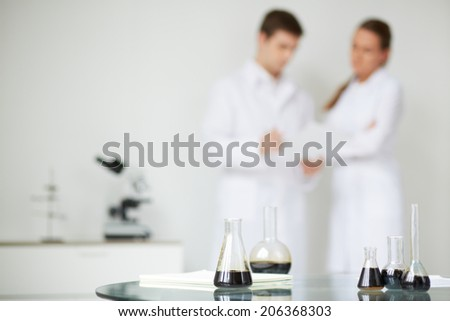 Test-tubes with liquid oil on background of two scientists working in laboratory