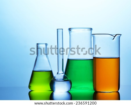Test tubes with liquid on bright blue background - stock photo