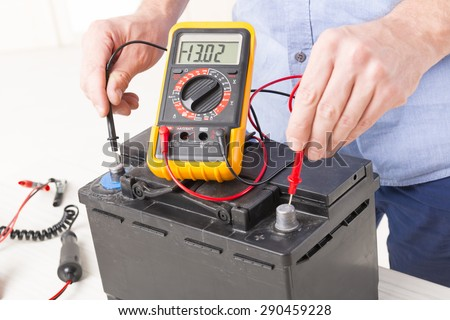 Testing car battery with digital multimeter - stock photo