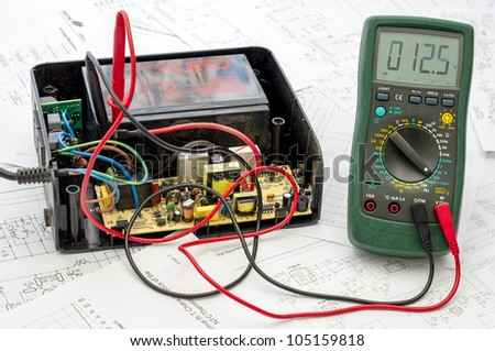 Testing old battery voltage with digital multimeter - stock photo