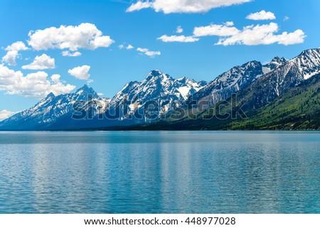 Teton Range at Jackson Lake - A spring view of still snow-covered Teton Range at shore of Jackson Lake in Grand Teton National Park, Wyoming, USA. - stock photo
