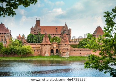 Teutonic Castle in Malbork (Marienburg) in Pomerania, Poland, Europe. UNESCO world heritage site. Blue sky with clouds in background and Nogat river in foreground.