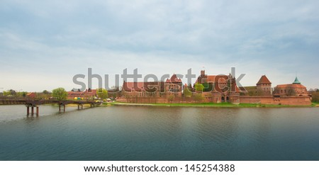 Teutonic castle Malbork in Pomerania region of Poland over Nogat river. UNESCO World Heritage Site. Knights' fortress also known as Marienburg. - stock photo