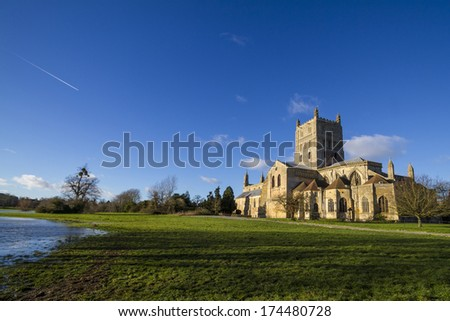 Tewkesbury Abbey, Gloucestershire, England founded by Robert FitzHamon in 1087 and completed in 1121. Surrounded by flood water. - stock photo
