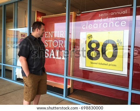 TEXAS, USA - AUGUST 18, 2017: A tall handsome American man wearing casual clothes smiles happily when seeing the discount banner of a clothes store.