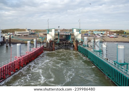 TEXEL, NETHERLANDS - NOVEMBER 2014: View on the ferry port of Texel from a ferry boat just leaving the Island on November 17th, 2014, near Texel. - stock photo