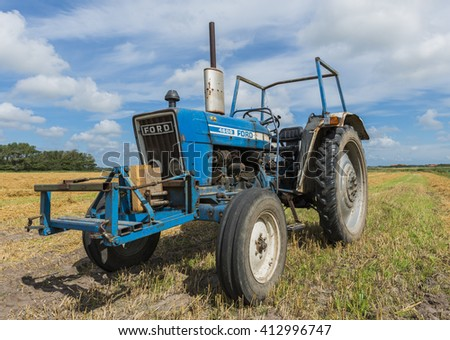 Texel, The Netherlands - August 23, 2012: Old blue tractot on a farm field in the country of the Wadden Isle.