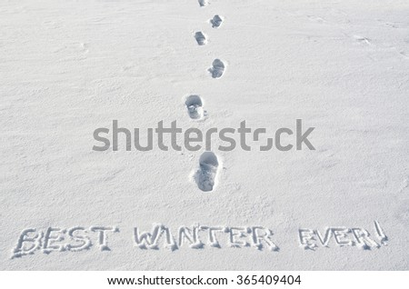 Text BEST WINTER  EVER hand written on snow background  and footsteps marks. Horizontal postcard template. - stock photo