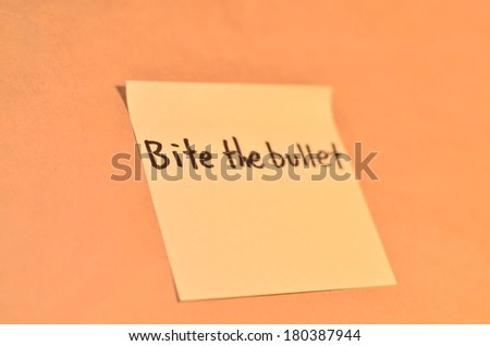 Text bite the bullet on the short note texture background - stock photo