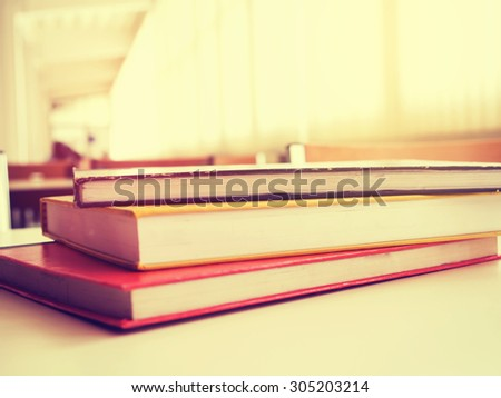 Text book on the desk in library and shallow dof. Vintage style photo. - stock photo