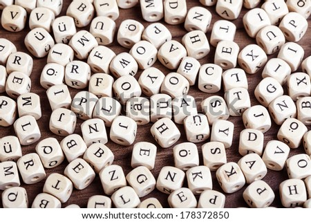 Text concept macro: Letter dices lying in chaos on table - stock photo