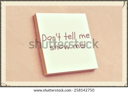 Text don't tell me show me on the short note texture background - stock photo