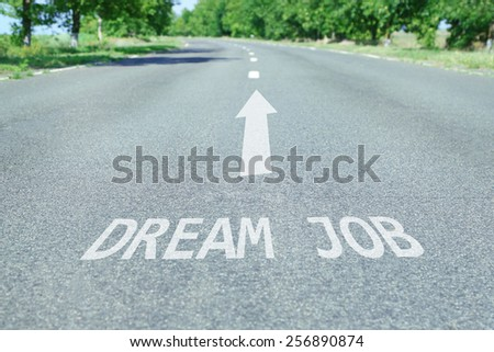 Text Dream Job with arrow marking on road surface - stock photo
