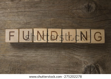 text FUNDING on a wooden background - stock photo