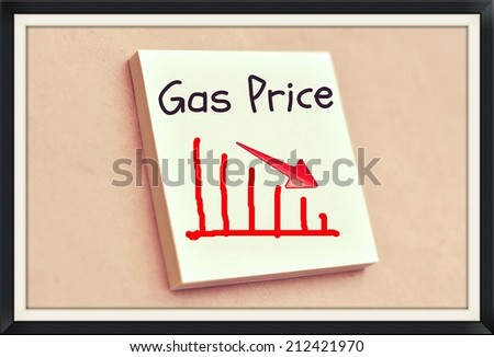 Text gas price on the graph goes down on the short note texture background - stock photo