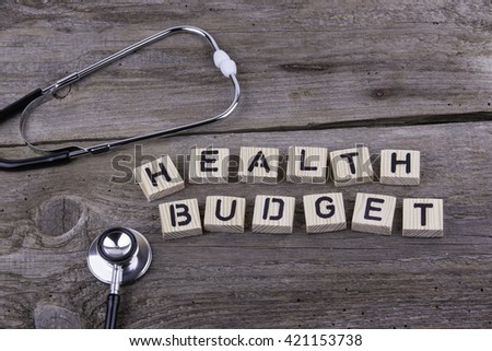 Text: HEALTH BUDGET from wooden letters on wooden background - stock photo