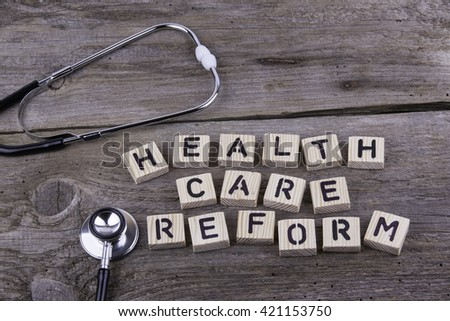 Text: HEALTH CARE REFORM from wooden letters on wooden background - stock photo