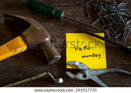 """Text """"Hello Monday"""" on yellow short note paper with old tools laying on natural wood desk, still  life image dark tone.  - stock photo"""
