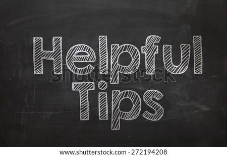 Text Helpful Tips handwritten with white chalk on a blackboard - stock photo