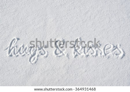 Text hugs and kisses hand written on snow background. Horizontal valentines postcard template. - stock photo