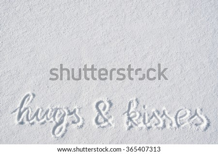 Text hugs and kisses hand written on snow background. Horizontal valentines postcard template. Space for copy, lettering.
