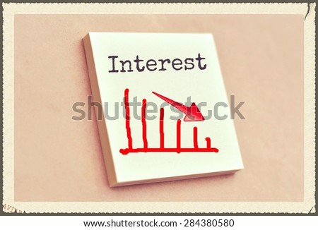 Text interests on the graph goes down on the short note texture background - stock photo