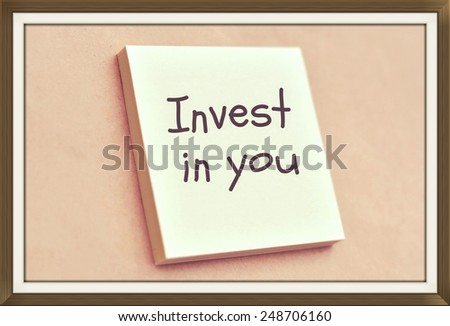 Text invest in you on the short note texture background - stock photo